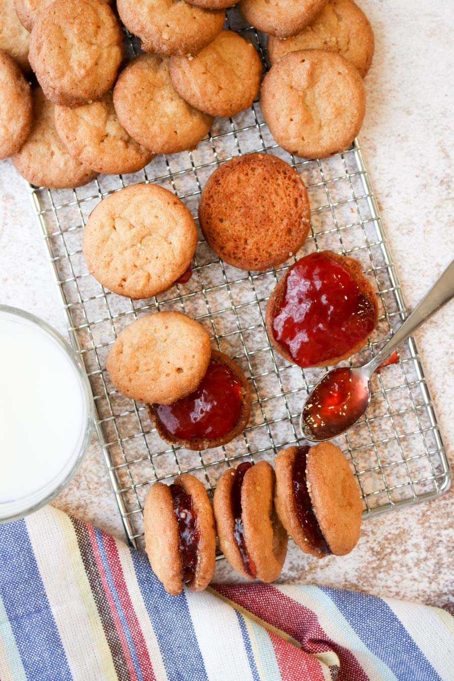 Peanut butter cookies on a cookie rack with strawberry jelly