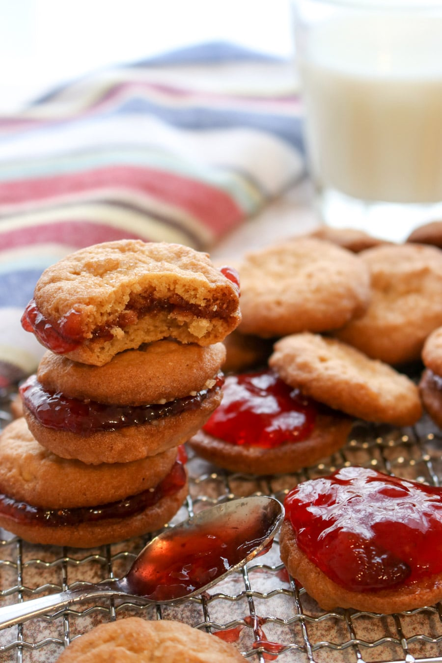 a stack of peanut butter and jelly cookies and a spoon of jelly on a cookie rack