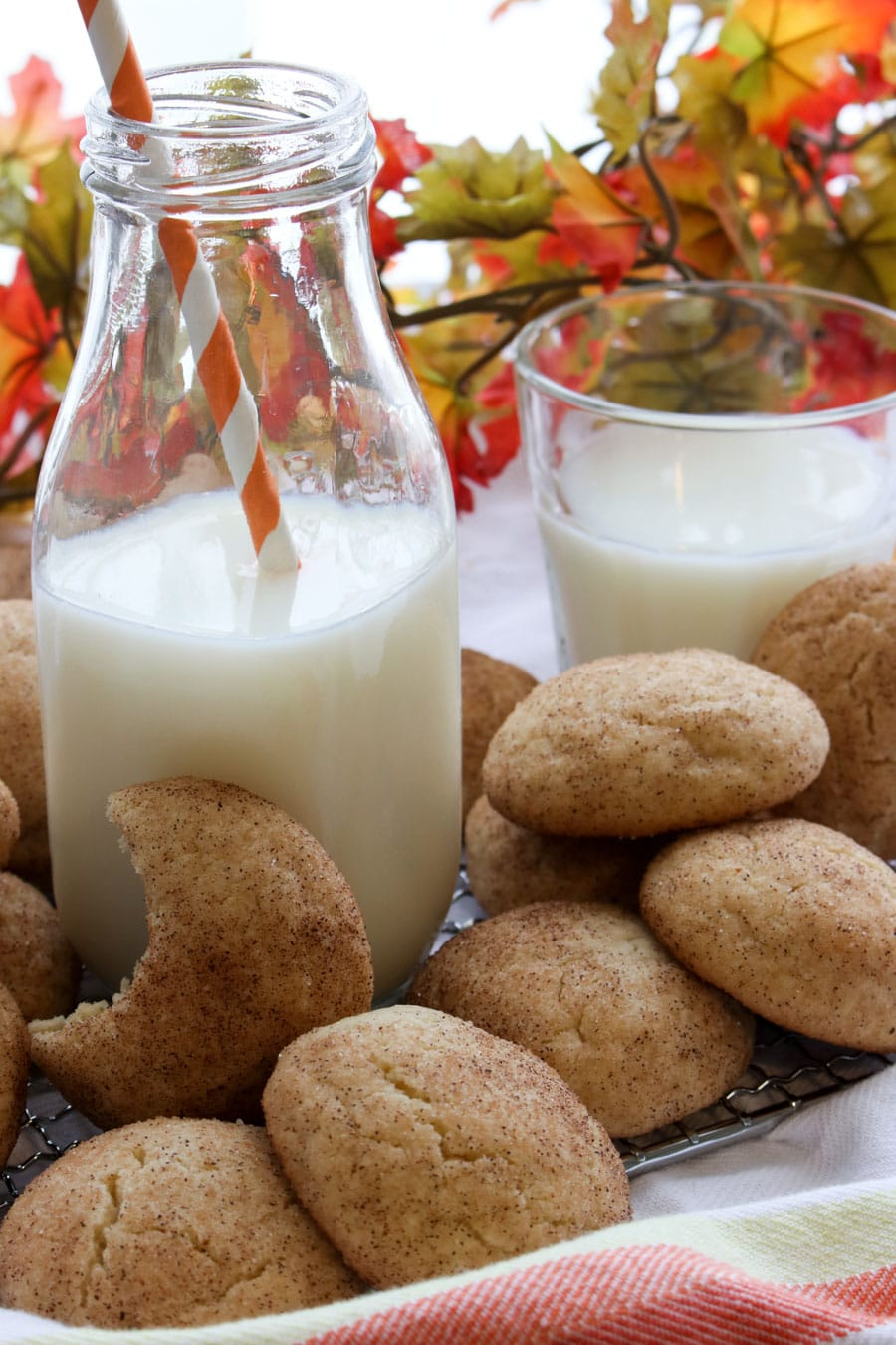 bottle of milk with orange straw and a glass of milk and cookies