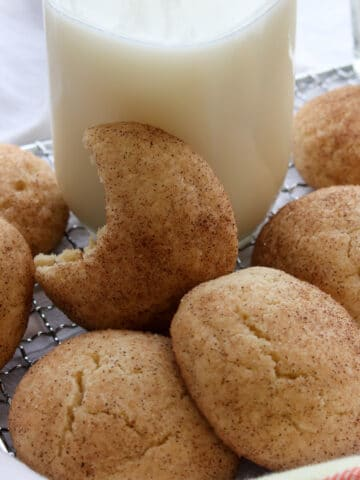 pile of cookie, one with a bite out of it leaning against a glass of milk