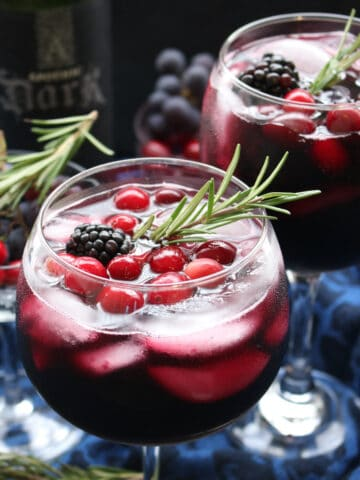 glass of red wine with a rosemary sprig.