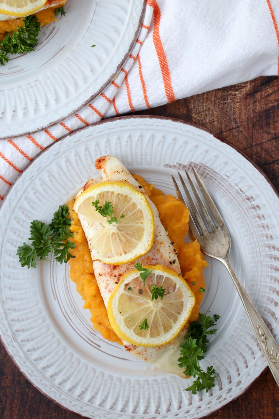 A piece of fish topped with lemon slices sitting on top of butternut squash puree