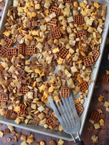 Chex party mix on a cookies sheet being scooped with a metal spatula