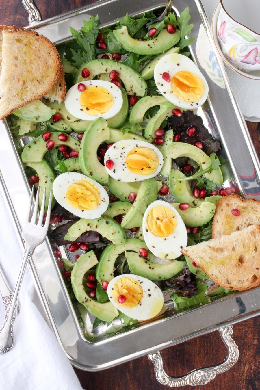 silver platter filled with lettuce, avocados, hard boiled eggs, pomegranate seeds and toast