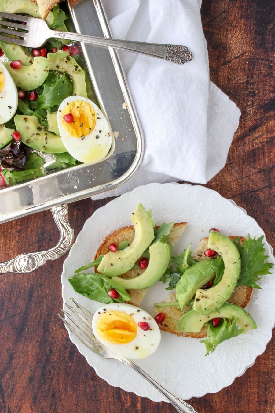 while plate with two slices of toast with sliced avocado on top and hard-boiled egg on the side, garnished with pomegranate seeds