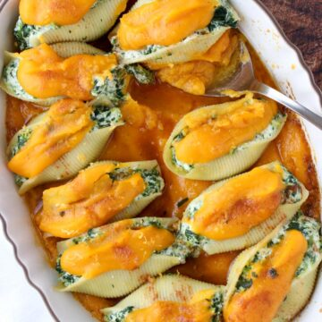 Casserole dish filled with stuffed shells topped with orange squash