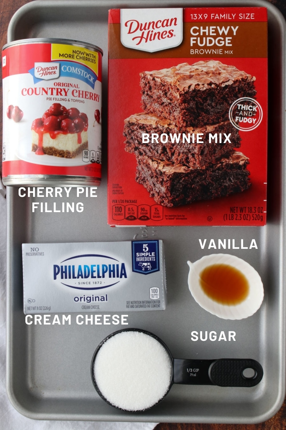 cookie sheet with the ingredient to make chocolate cherry cheesecake brownies