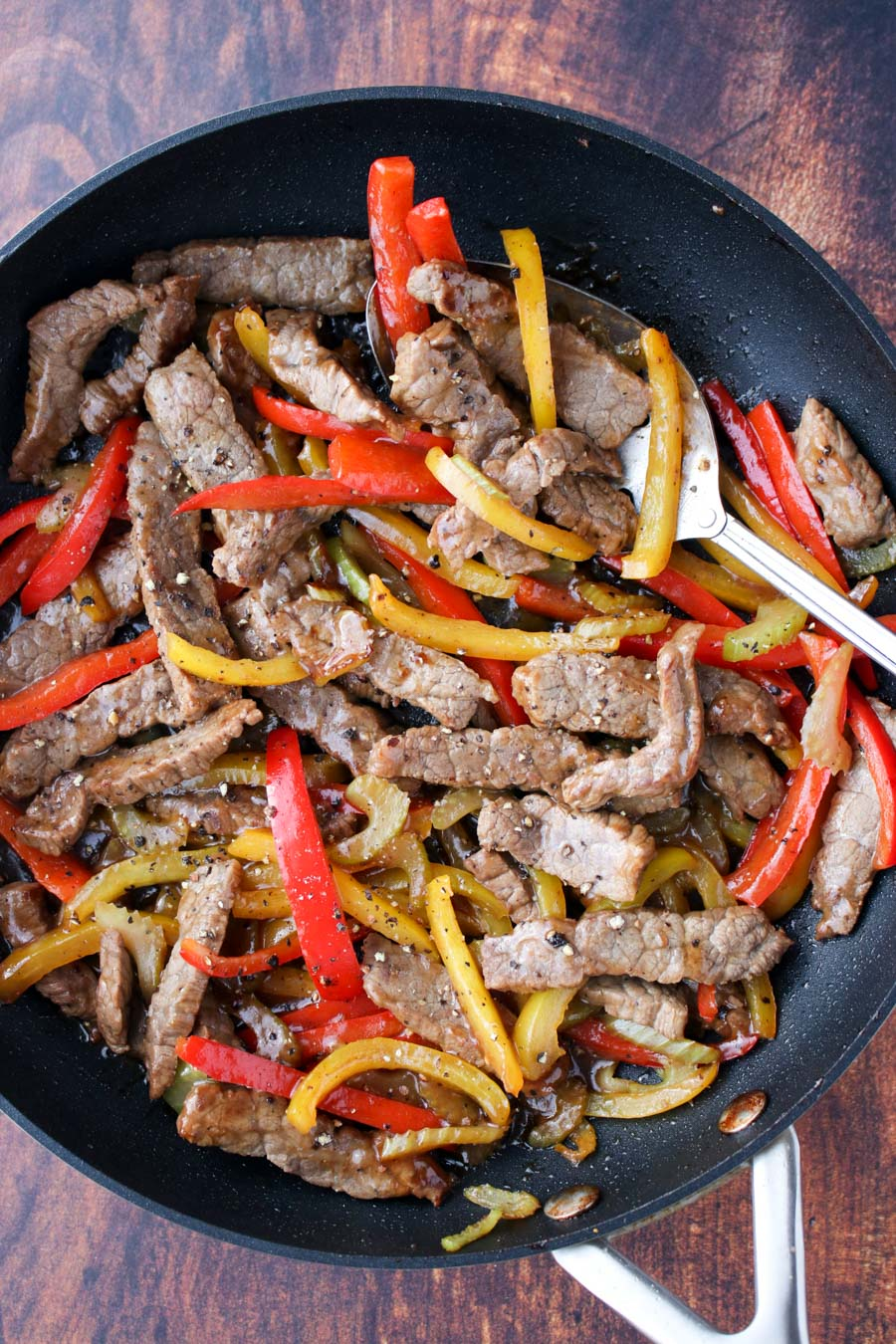 Skillet filled with beef strips and red and yellow bell peppers