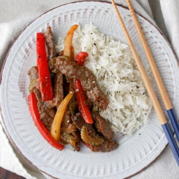 White plate with beef, red and yellow bell pepper slice, with side of rice and chop sticks