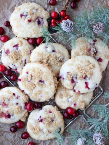 muffin top cookies on a wire rack with fresh cranberries and greens around them