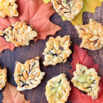 leaf shaped cookies spread out over fall colored leaves
