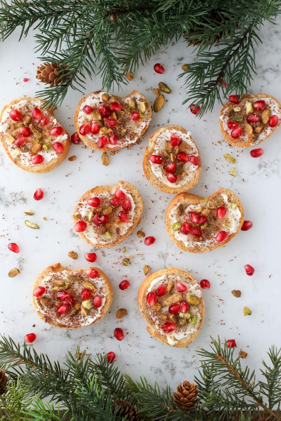 Pistachio Pomegranate Crostini  on a marble background with greens on top and bottom