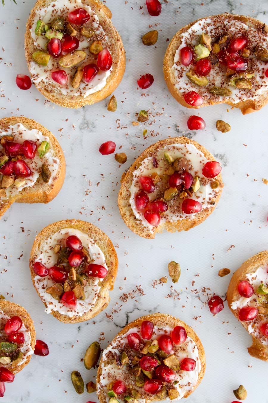 Small toast rounds topped with cream cheese, nuts, and pomegranate seeds