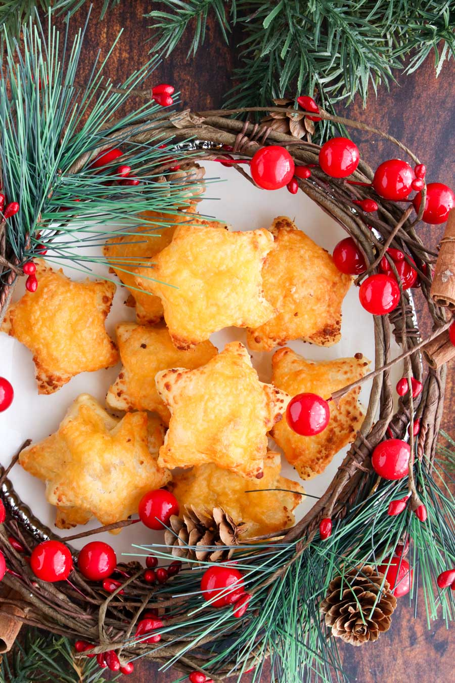 Cheese stars on a play with surrounded by Christmas decorations of holly and pine