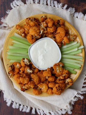 yellow plate with buffalo cauliflower and celery with blue cheese dip in the middle