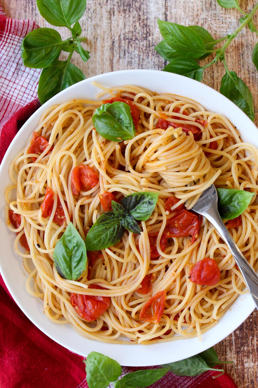 Bowl of pasta with tomatoes and pasta swirled around a fork