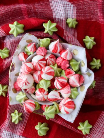 A bowl of colorful meringues on a red cloth