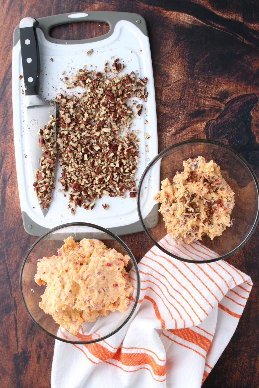 Pimento cheese in a bowl with a cookie sheet of chopped pecans