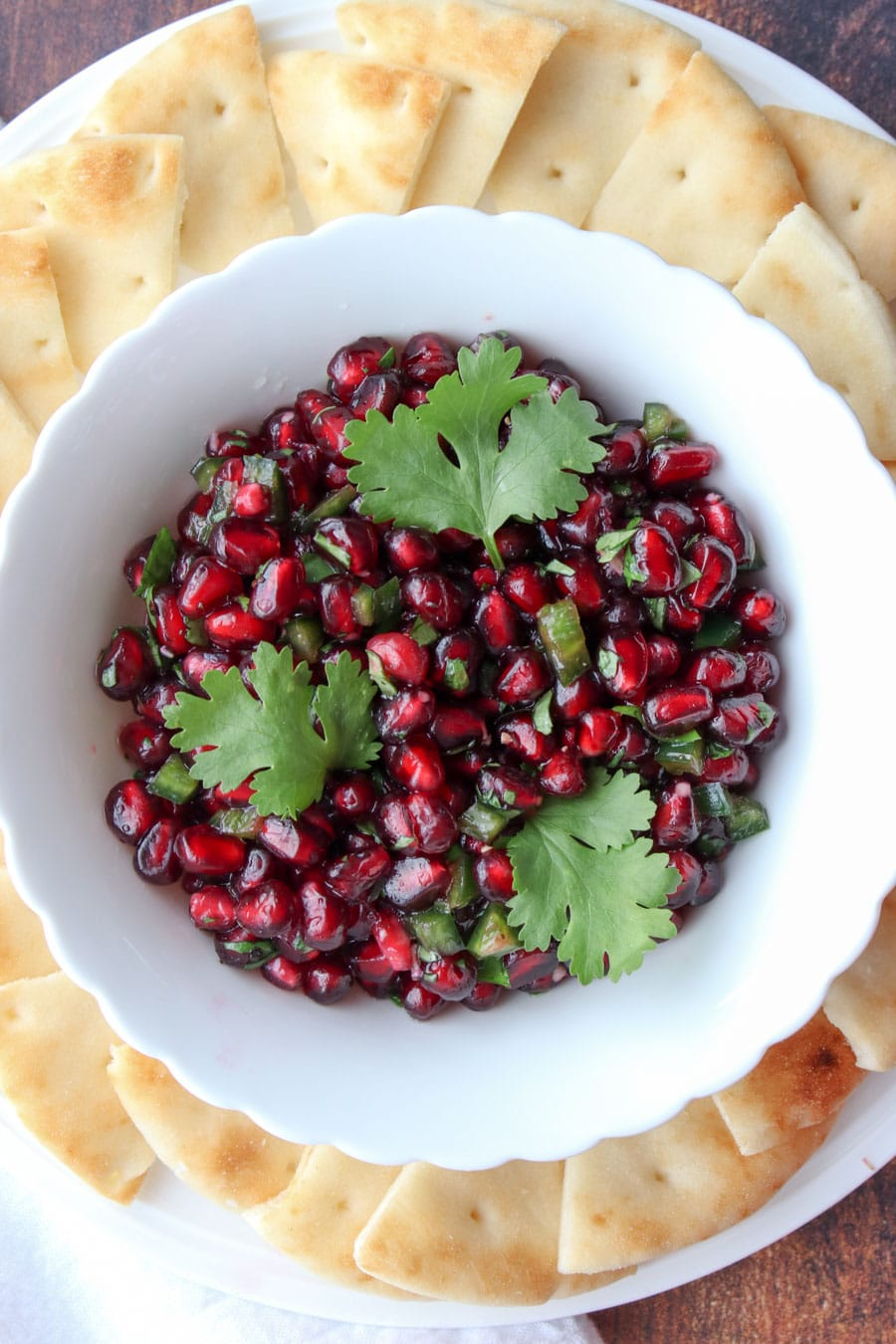 bowl of pomegranate salsa surrounded by crackers