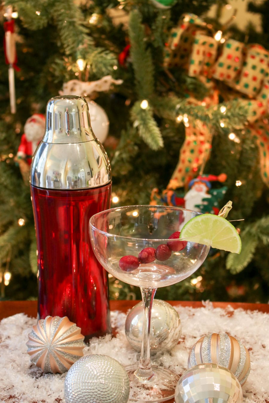 empty martini glass with a red shaker next to it. Christmas tree in the background.
