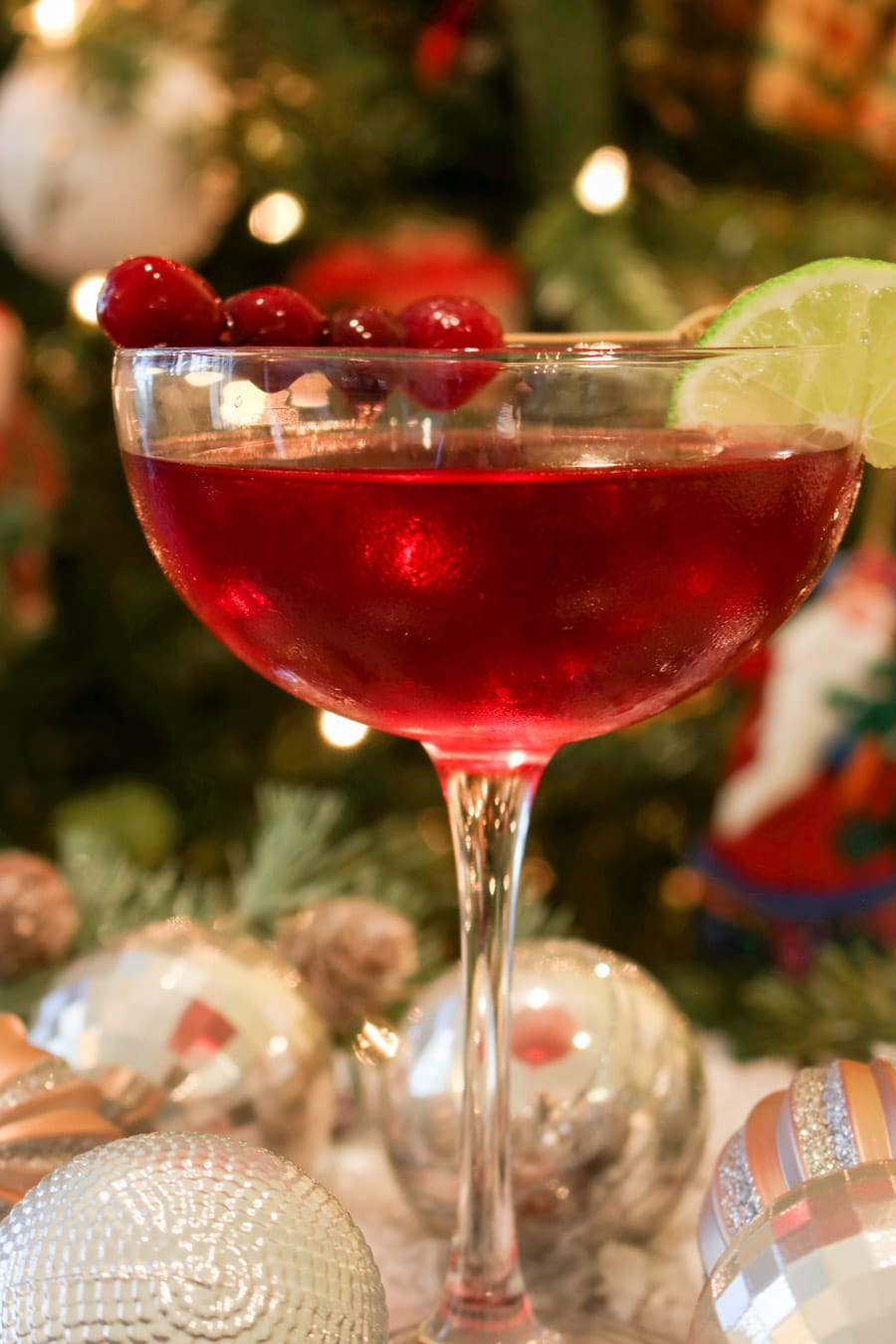 Scarlet colored cocktail in from of a Christmas tree