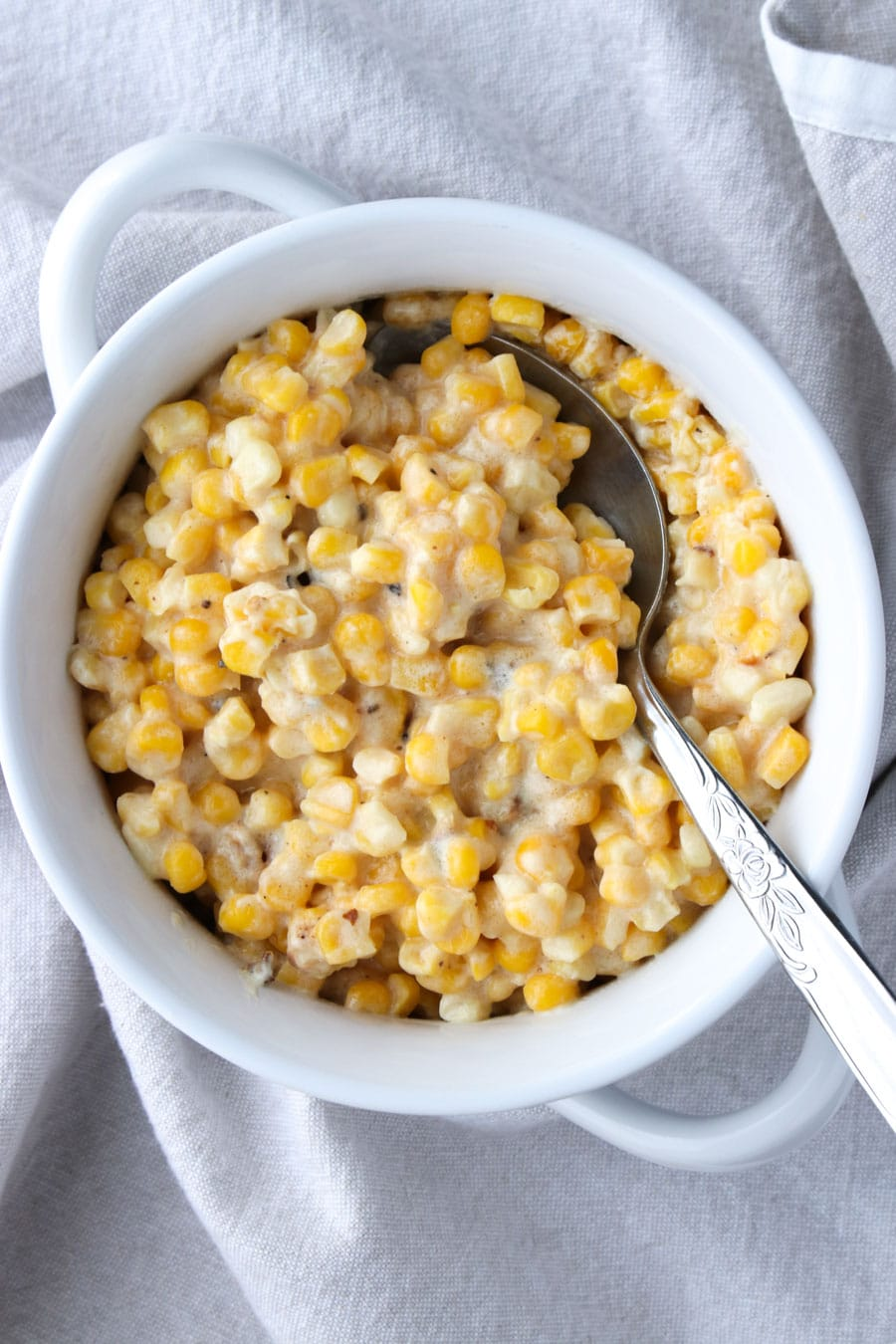 white bowl filled with creamed corn with a serving spoon on a gray napkin