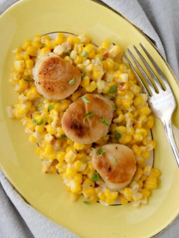platter of creamed corn topped with three scallops