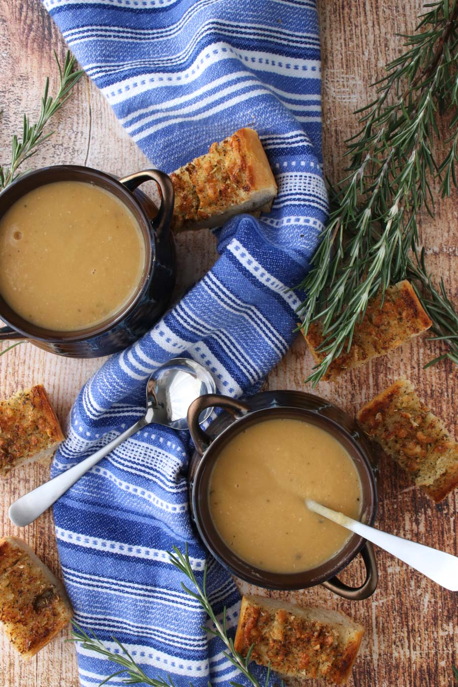 2 bowls of soup with a blue napkin and fresh rosemary sprigs and garlic toast
