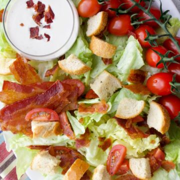 Platter of lettuce, tomatoes, bacon, croutons, and dressing