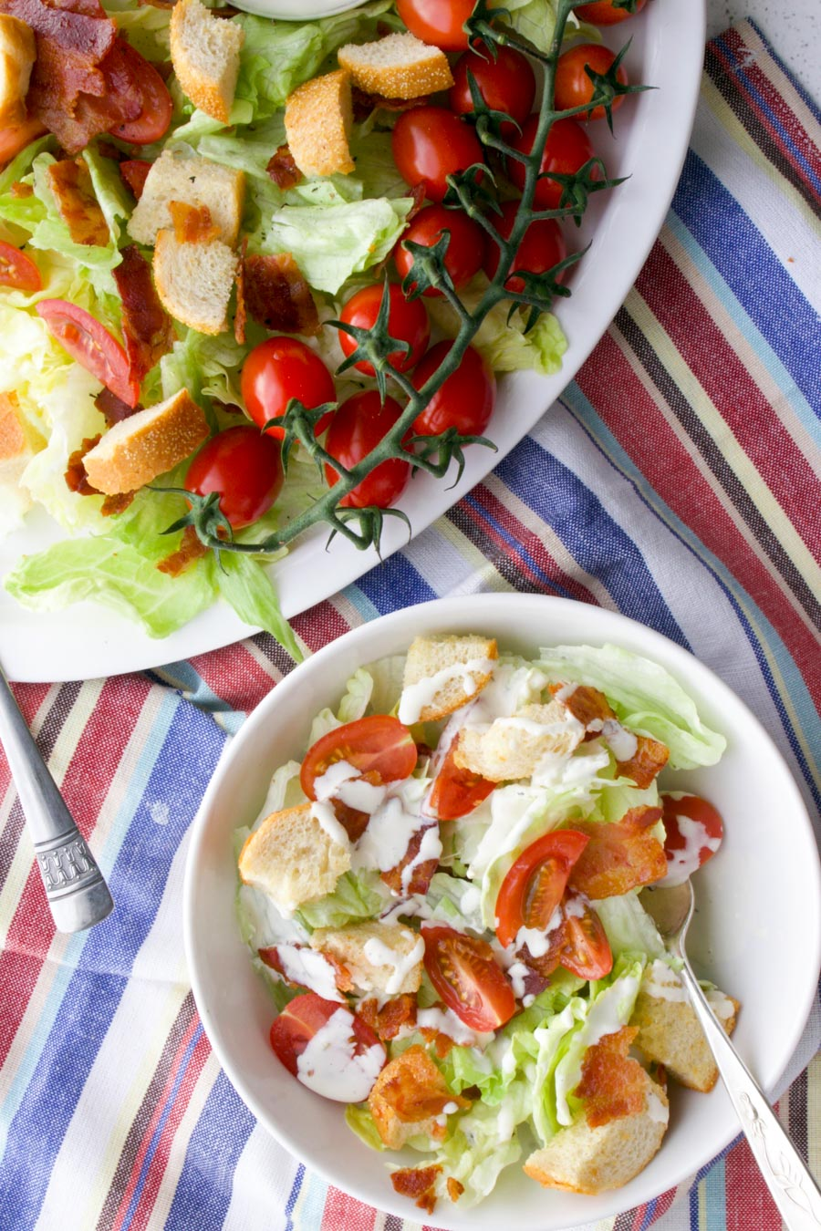small bowl of salad next to the larger platter of salad sitting on a red, white, blue cloth