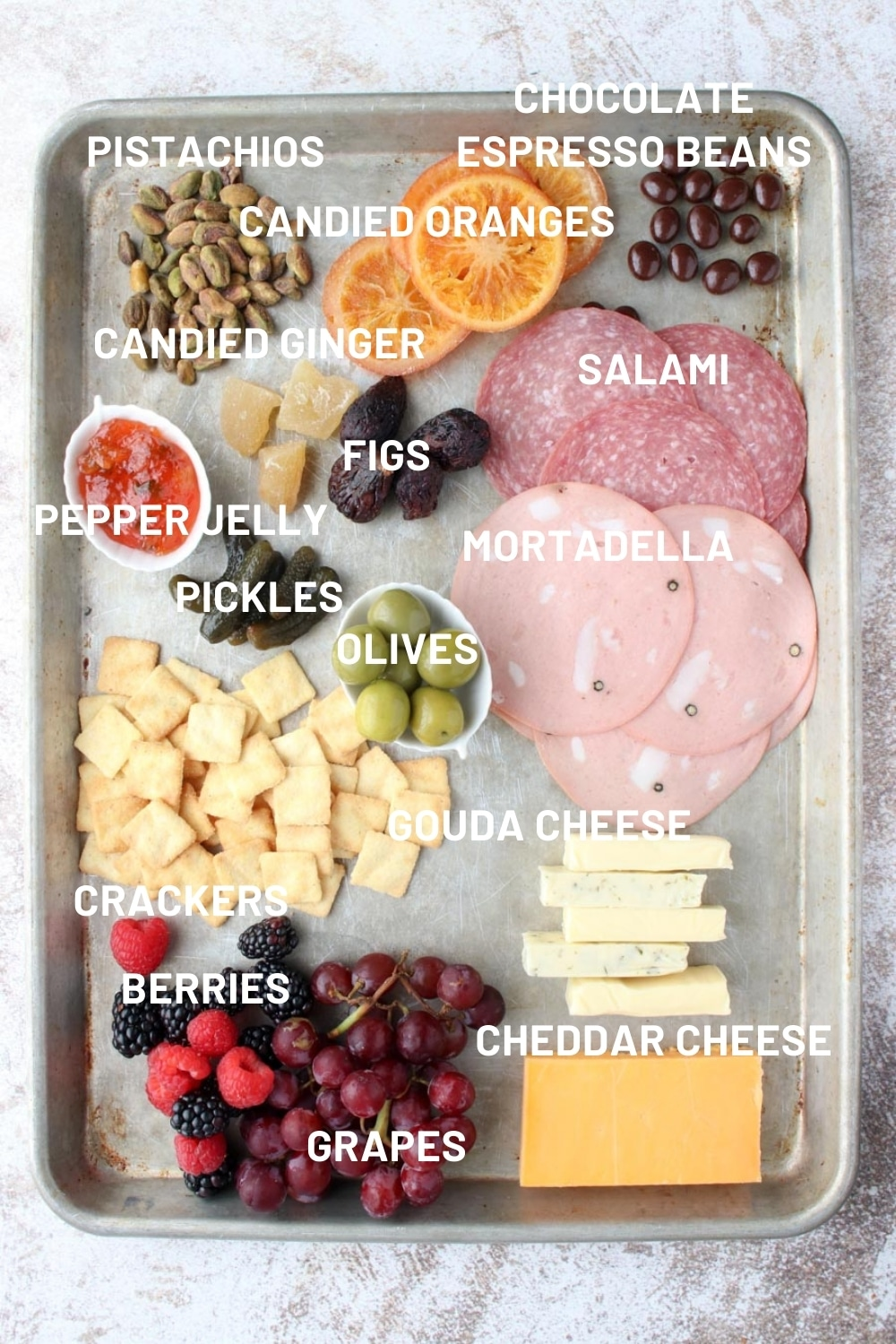 A sheet pan with all of the ingredients need to make a charcuterie platter for two.