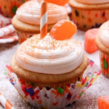 Orange cupcakes with a slice of candy and a straw on top