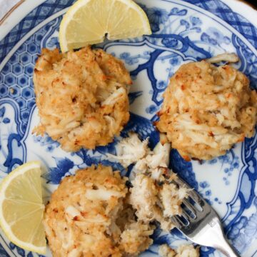 blue and white plate with three crab cakes, two slices of lemon and fork