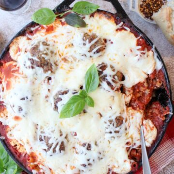 cast iron skilled of baked meatballs and pasta covered in cheese