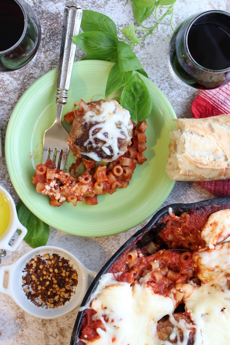 green plate with a meatballs, pasta, bread, and wine