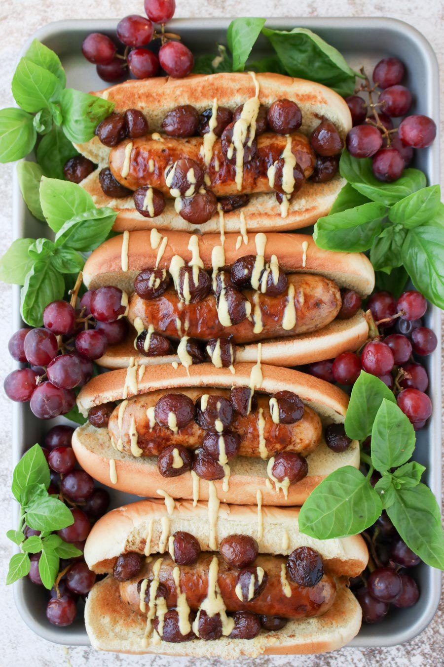 a tray with four sausages in buns topped with grapes and fresh basil