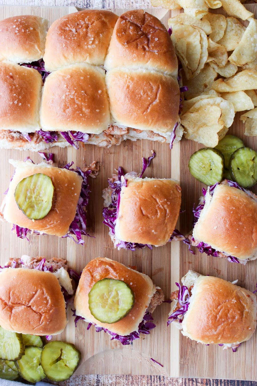BBQ Sliders on a serving board with pickles and chips