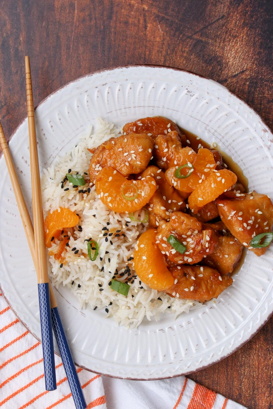 white plate with orange chicken and rice and chop sticks