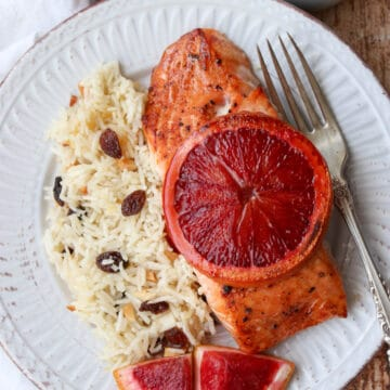Salmon filet with sliced blood orange on top with a side of rice