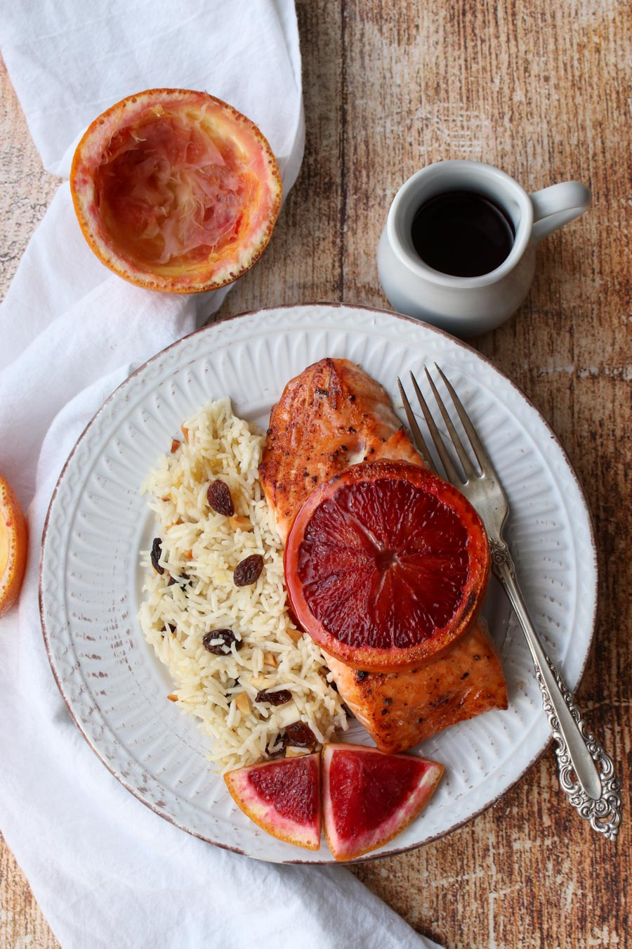 plate of salmon with orange slice on top and side of rice