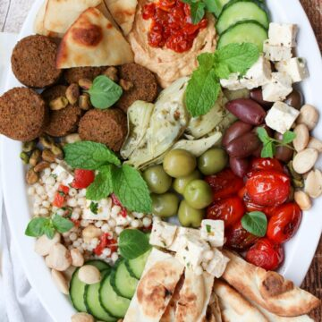 Platter of assorted Mediterranean foods on a large white oval plate