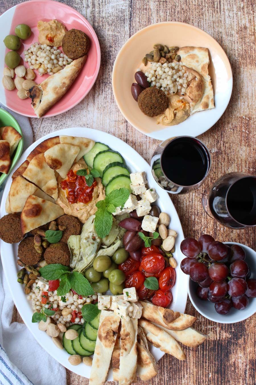 overhead shot of a mezze platter, two glasses or wine, and small plates