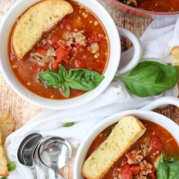 two bowls of sausage and bean soup with large croutons