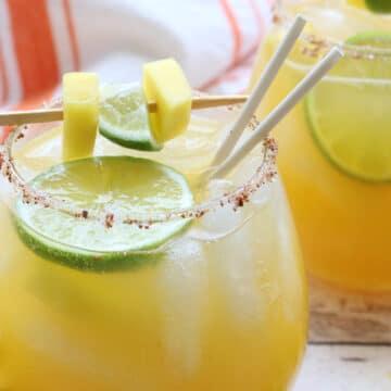 glass of mango margarita with garnish and straws