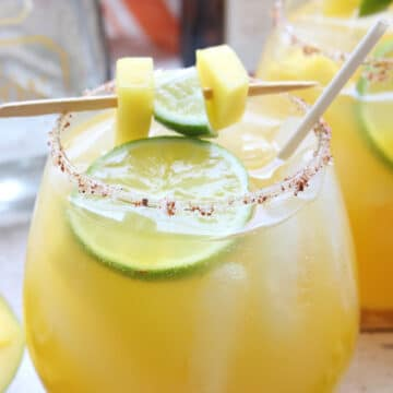 glass of mango margarita with lime and mango garnish