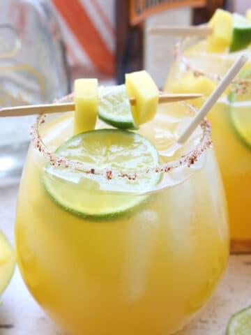 glass of mango margarita with lime and mango garnish