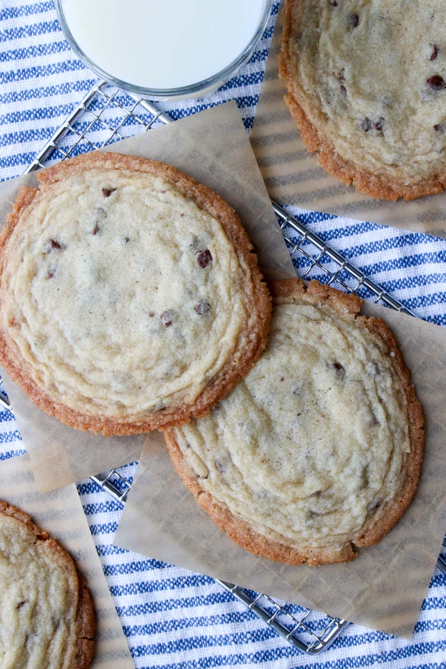 Giant chocolate chip cookies with a glass of milk on the side