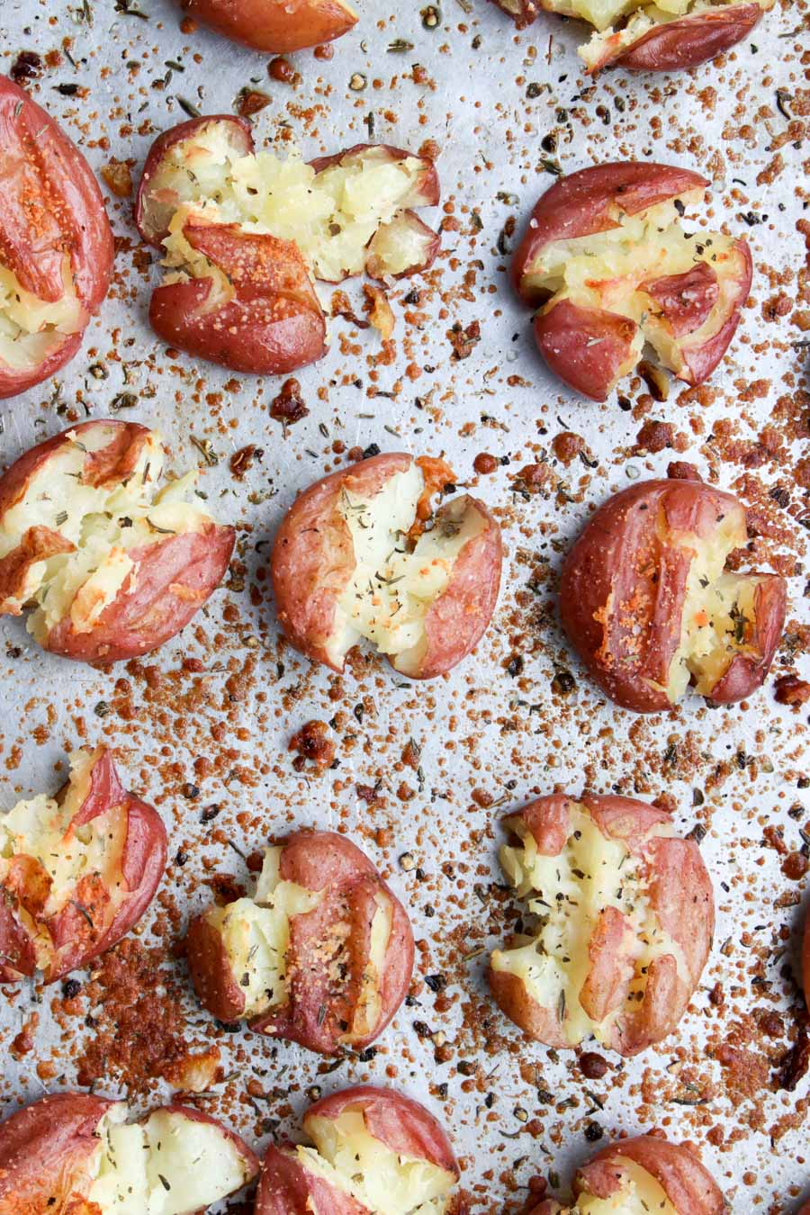 close up photo of smashed potatoes on a cookie sheet