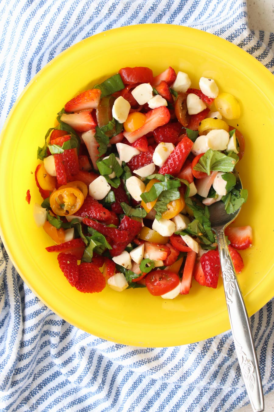 yellow bowl with strawberry cypress salad in it