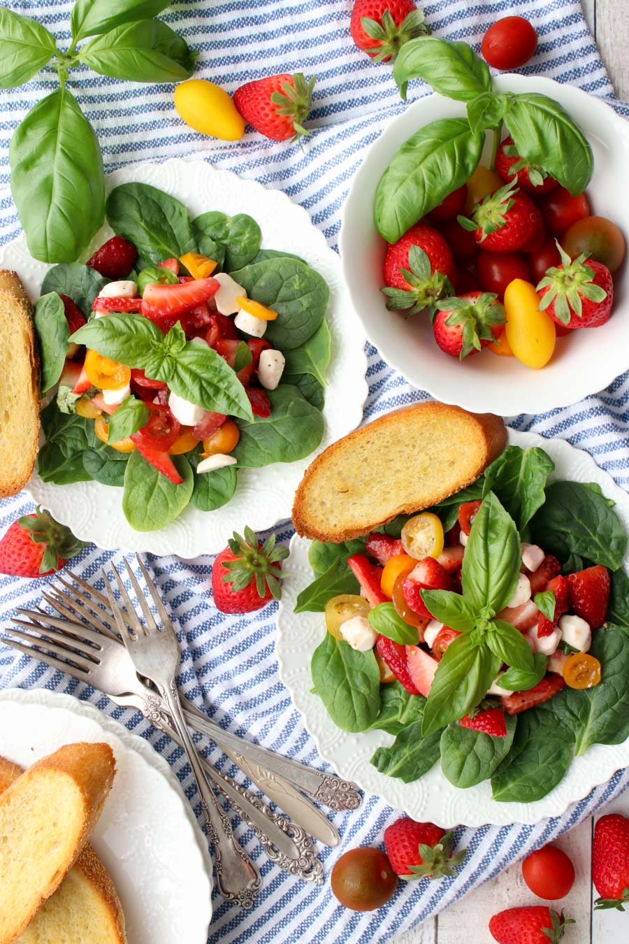 two strawberry cypress salads and a bowl of fresh strawberries